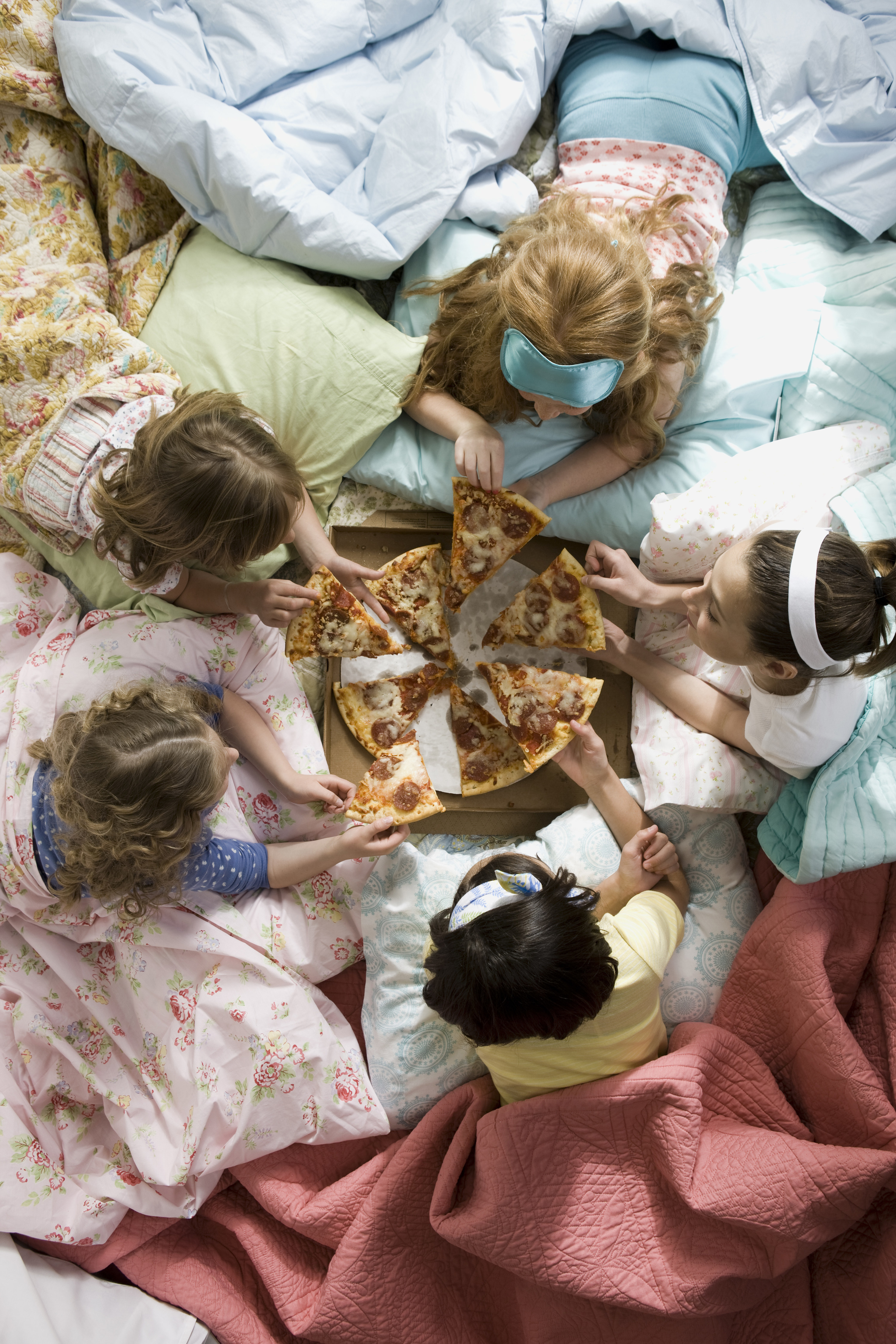 Five girls are cuddled up in blankets all facing each other, while they talk and eat slices of pepperoni pizza