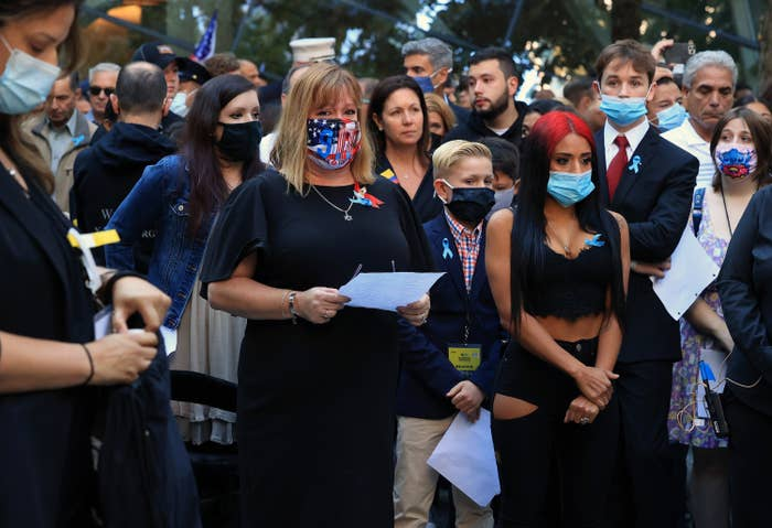 Somber people, most wearing masks, stand together