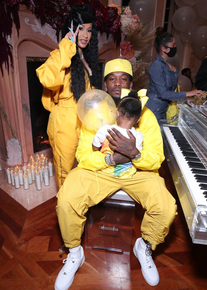 Cardi standing next to Offset is sitting at a piano while holding their daughter Kulture