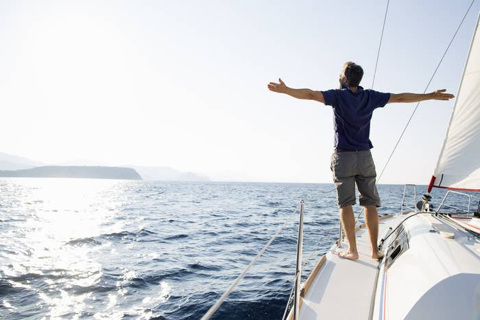 A man standing on a boat with his arms outstretched