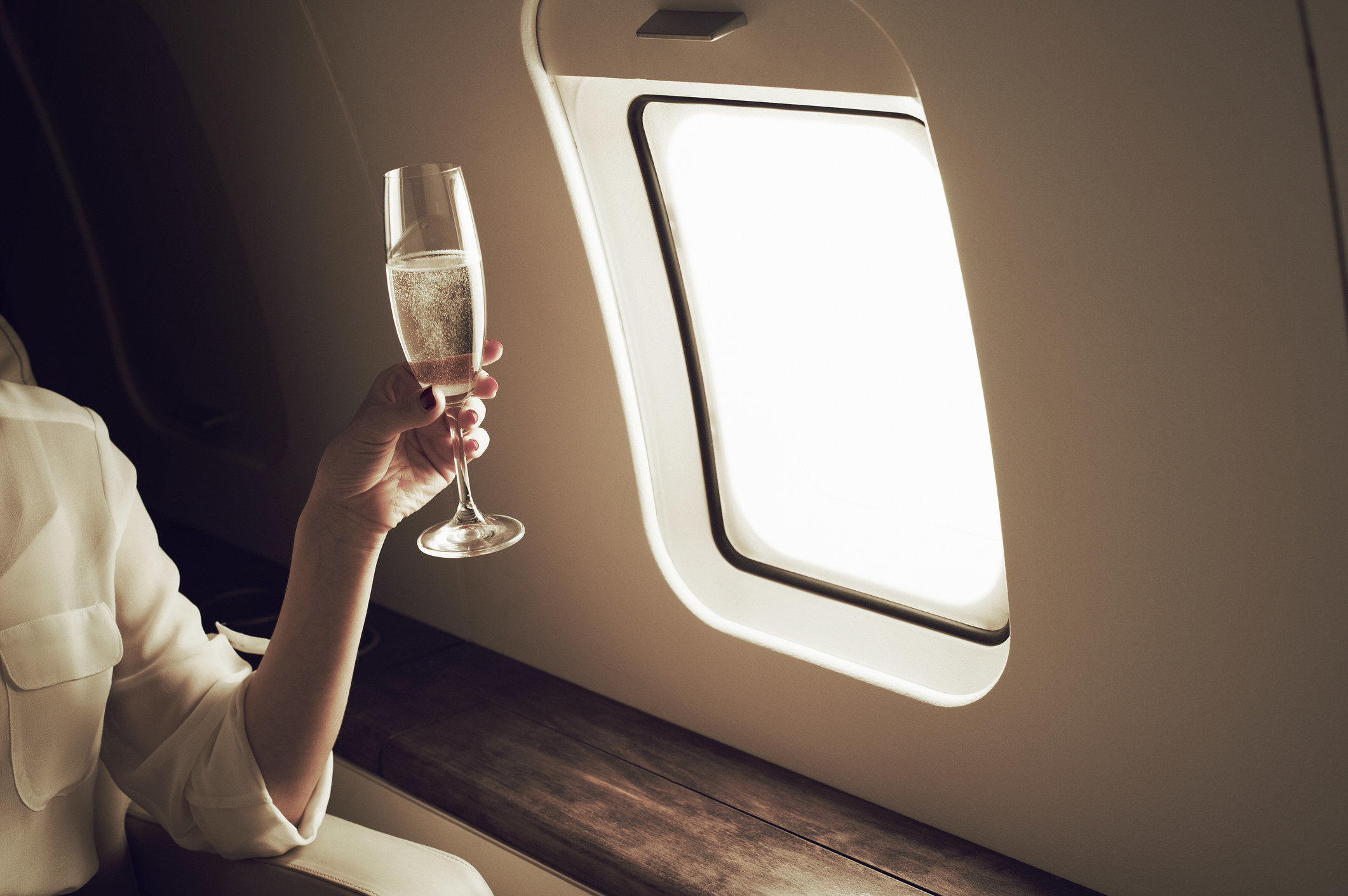 A person holding a glass of champagne while sitting in the window seat of the plane