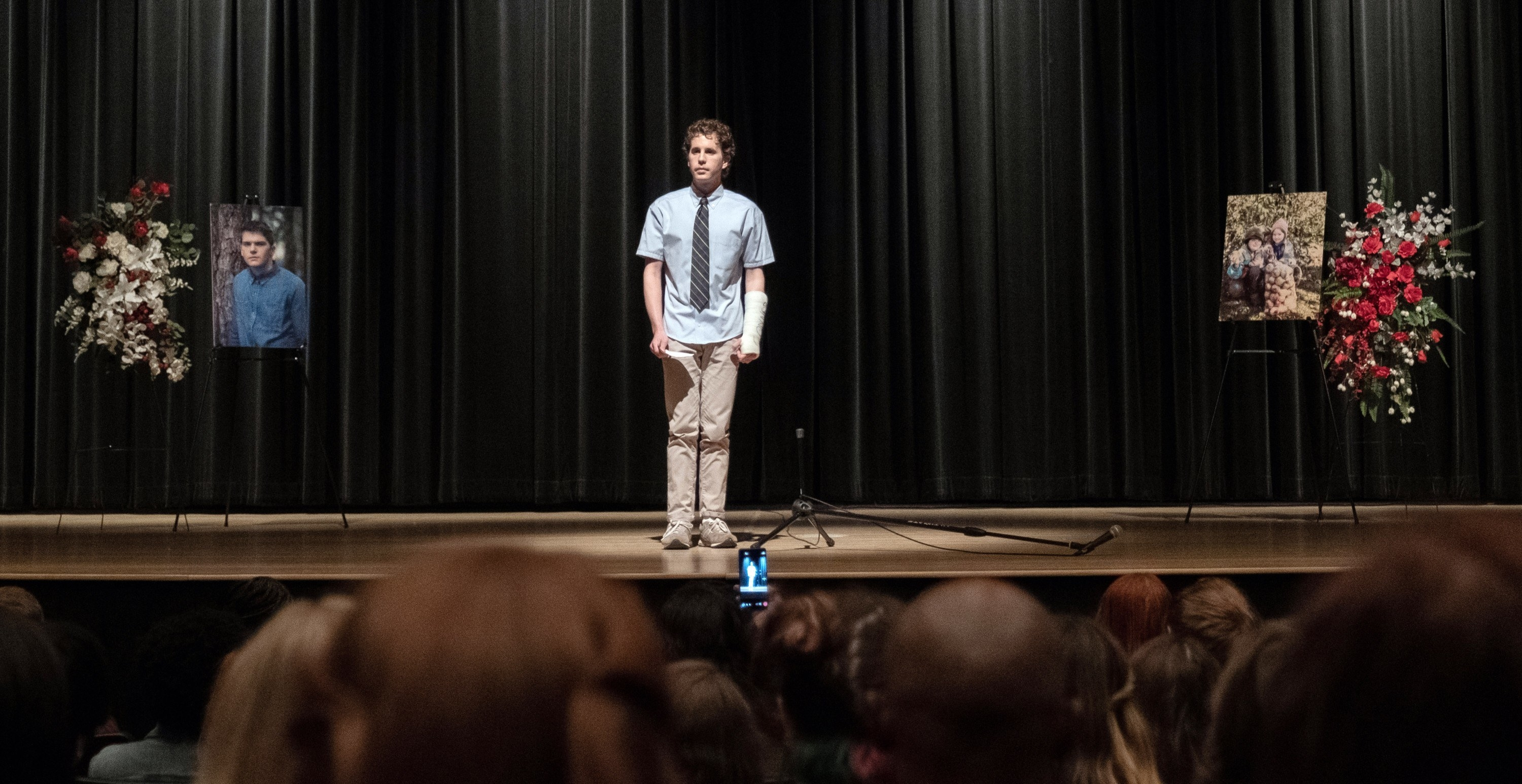 Evan Hansen standing at the mic in a school auditorium with pictures of a fellow student who has died off to the sides