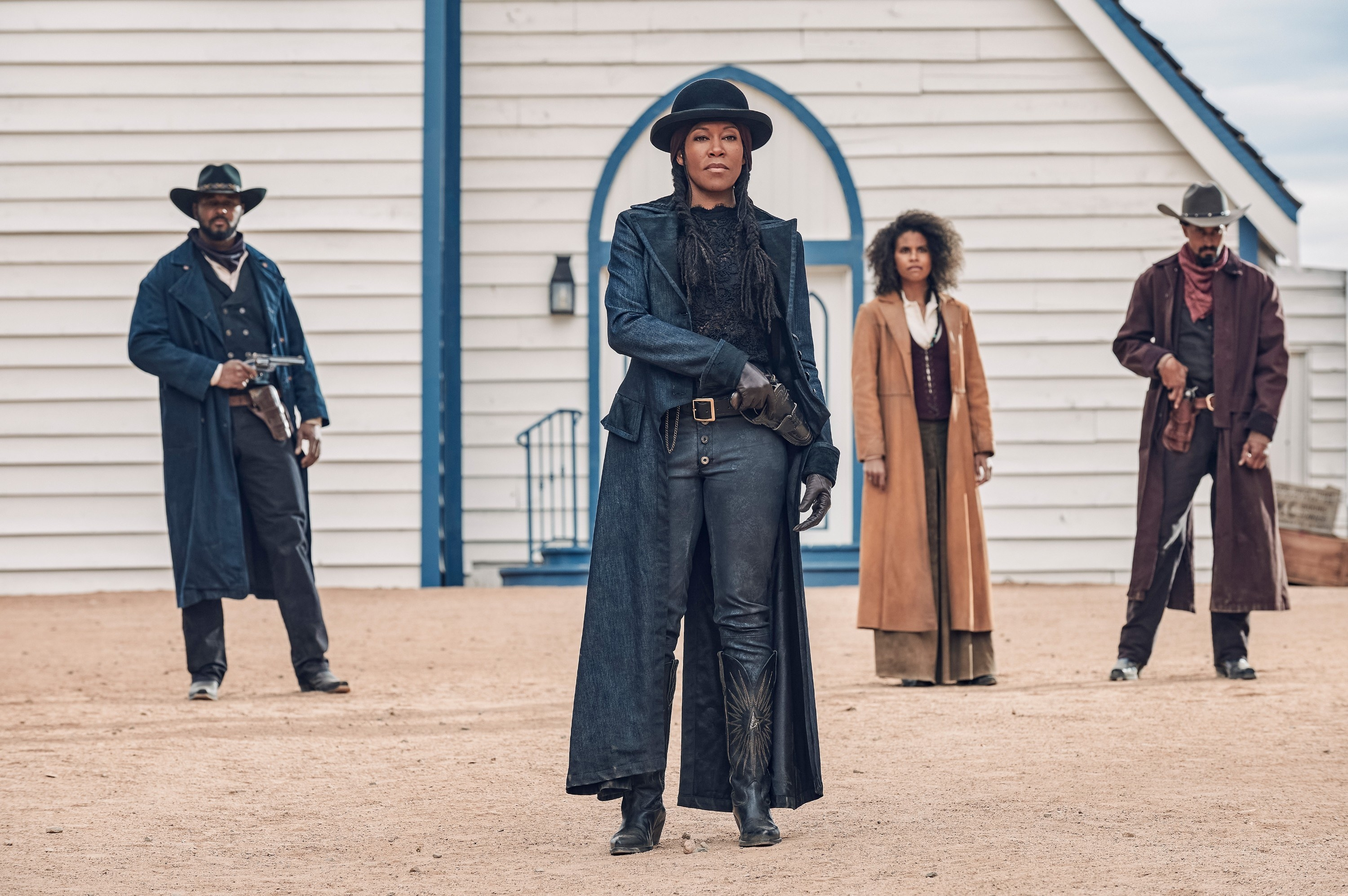 Regina King, Zazie Beets, and two other members of the cast standing in an open space guns at the ready