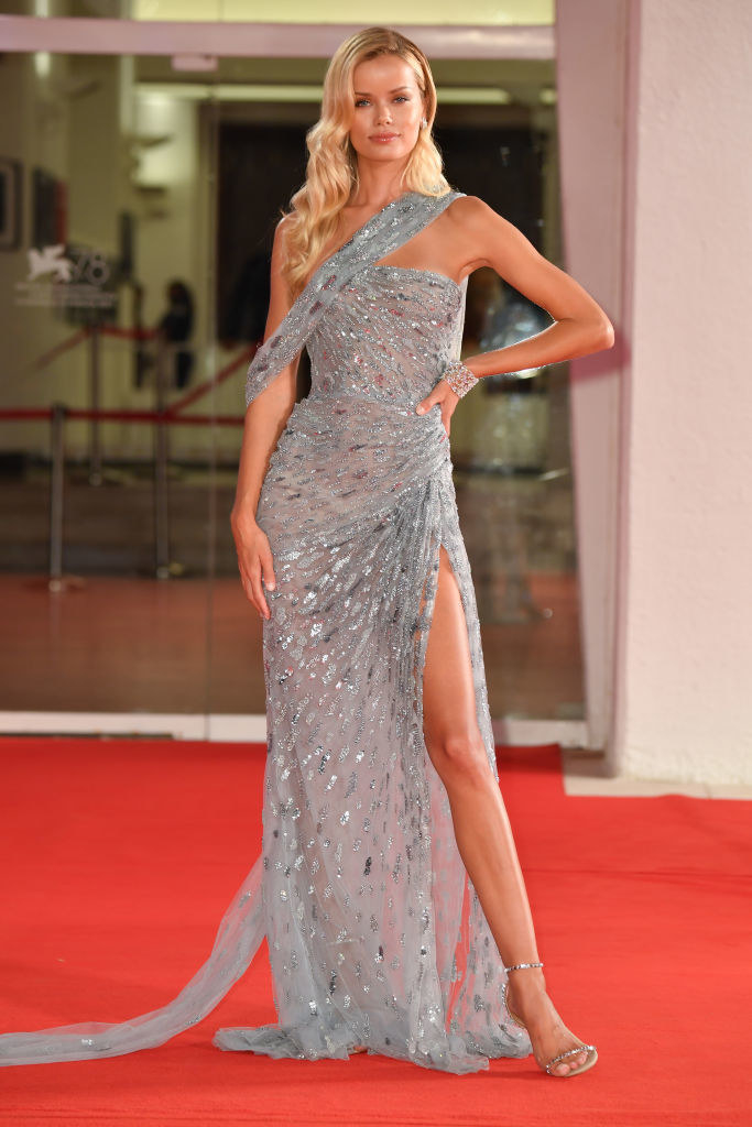 """Frida Aasen on the """"Halloween Kills"""" red carpet in a one-shoulder, glittery silver gown with a high slit"""