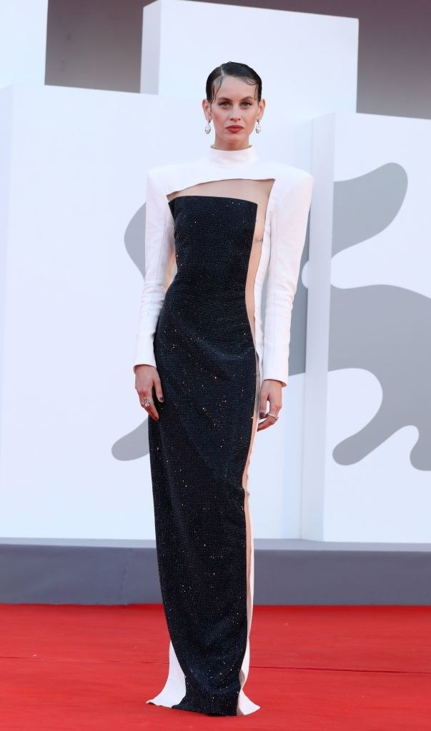 """Milena Smit attends the red carpet of the movie """"Madres Paralelas"""" in a black and white cut out gown"""