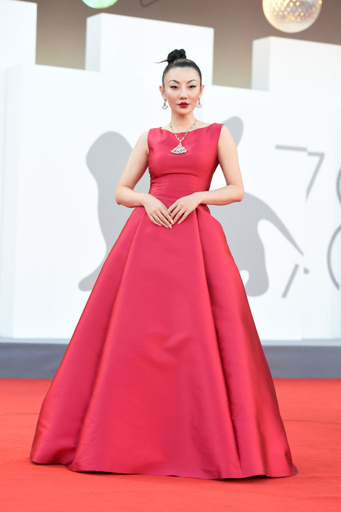 """Jessica Wang attends the red carpet of the movie """"Illusions Perdues"""" in a high neck satin red gown"""