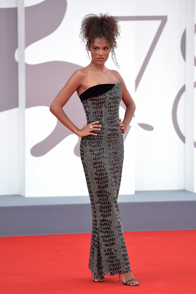 """Tina Kunakey attends the red carpet of the movie """"Dune"""" in a fitted black gown"""