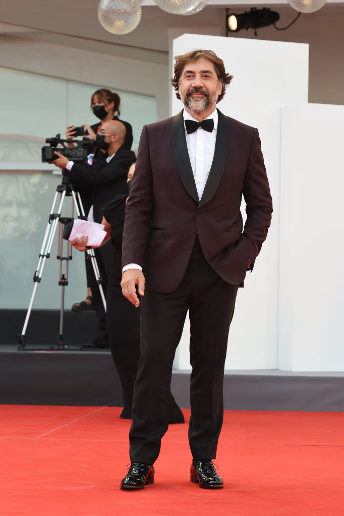 """Javier Bardem attends the red carpet of the movie """"Dune"""" in a maroon tuxedo jacket with black trousers"""