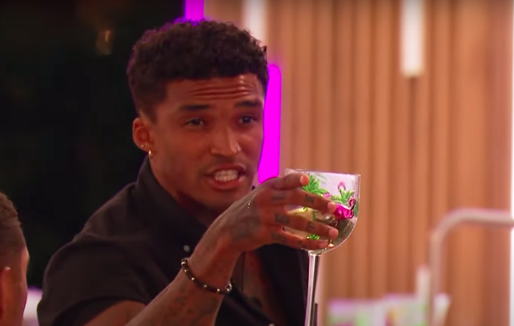 Michael speaking angrily while holding a glass