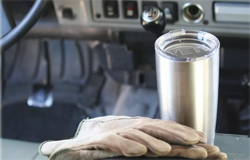 A stainless steel coffee tumblr in a truck with gloves next to it