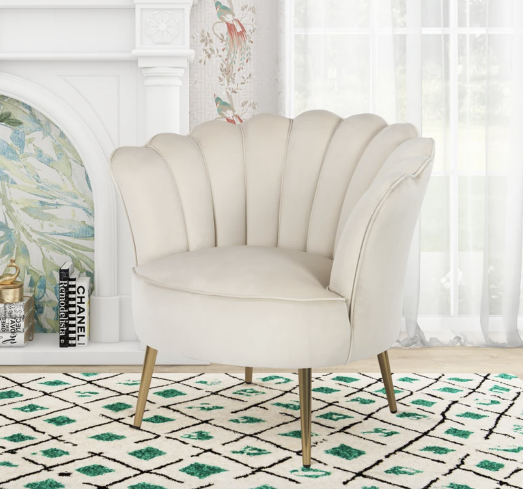 A cream colored chair sits in front of a fireplace