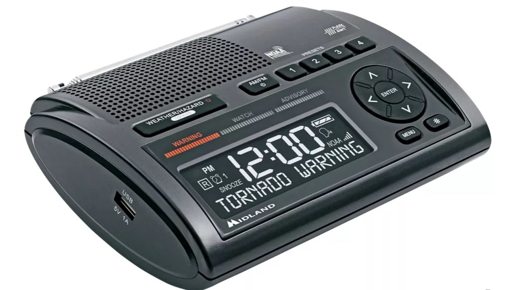 A black weather alert radio with buttons and a display that says 12:00 TORNADO WARNING