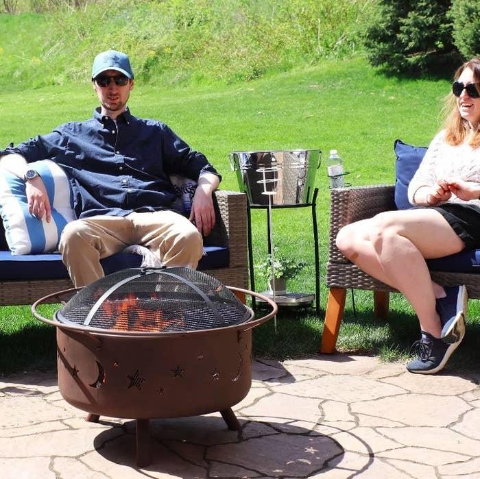 Two people enjoying a bonfire outside with the fire pit