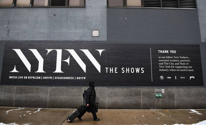 A person walking by a painted sign advertising New York Fashion Week