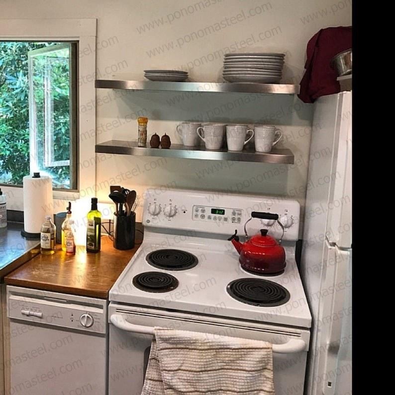 a kitchen with the stainless steel shelves above the oven