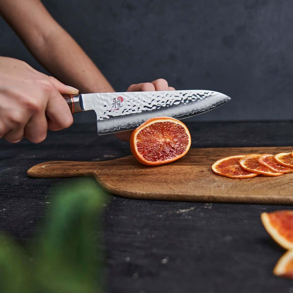 a and using the knife to thinly slice a grapefruit