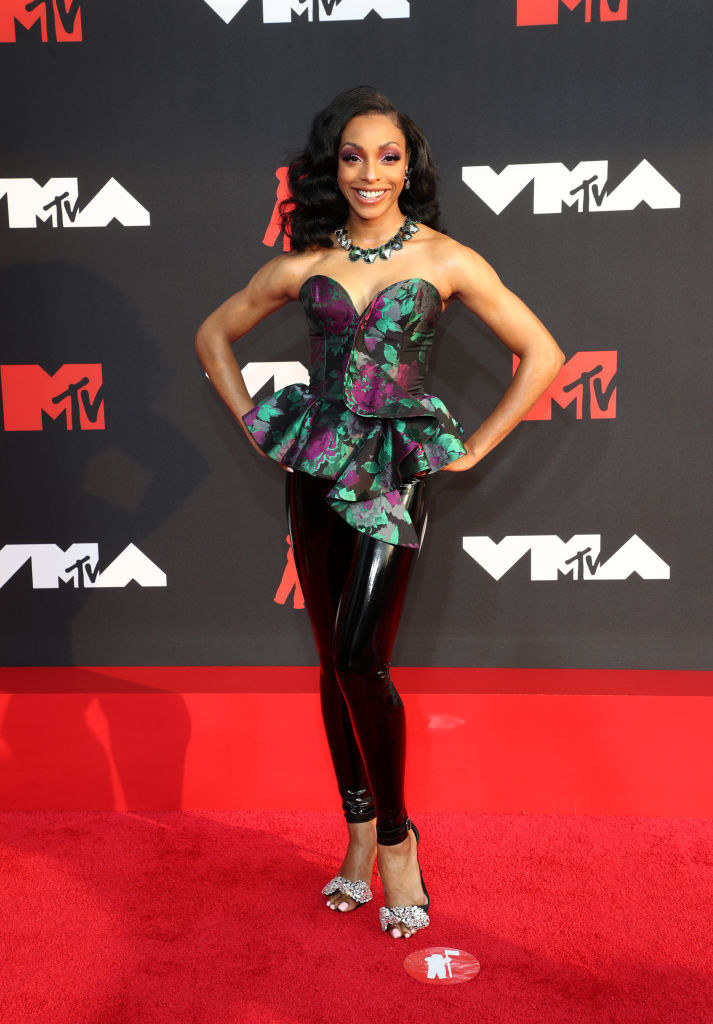 Jamila Mustafa on the red carpet in a multicolored, flared top and black slacks
