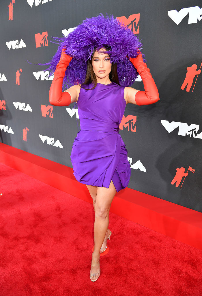 Kacey Musgraves in a short high neck purple dress with elbow length red gloves
