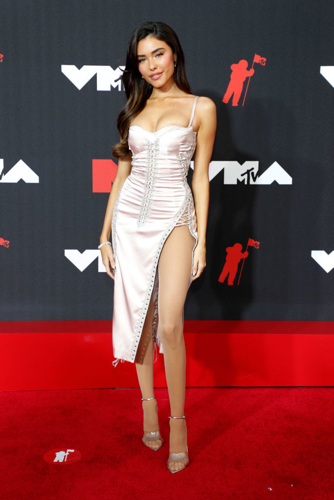 Madison Beer on the red carpet in a form-fitting, knee length light pink dress with a high slit