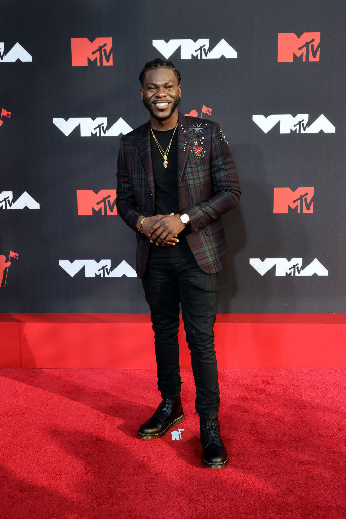 Dometi Pongo on the red carpet in a navy and red plaid blazer and black slacks