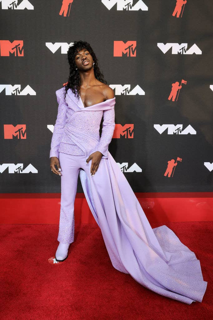 Lil Nas X on the red carpet in a suit-gown hybrid and a shoulder-length wig