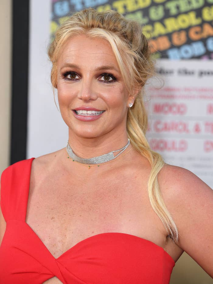 Britney Spears poses for a photo at a red carpet event while wearing an off-the-shoulder dress