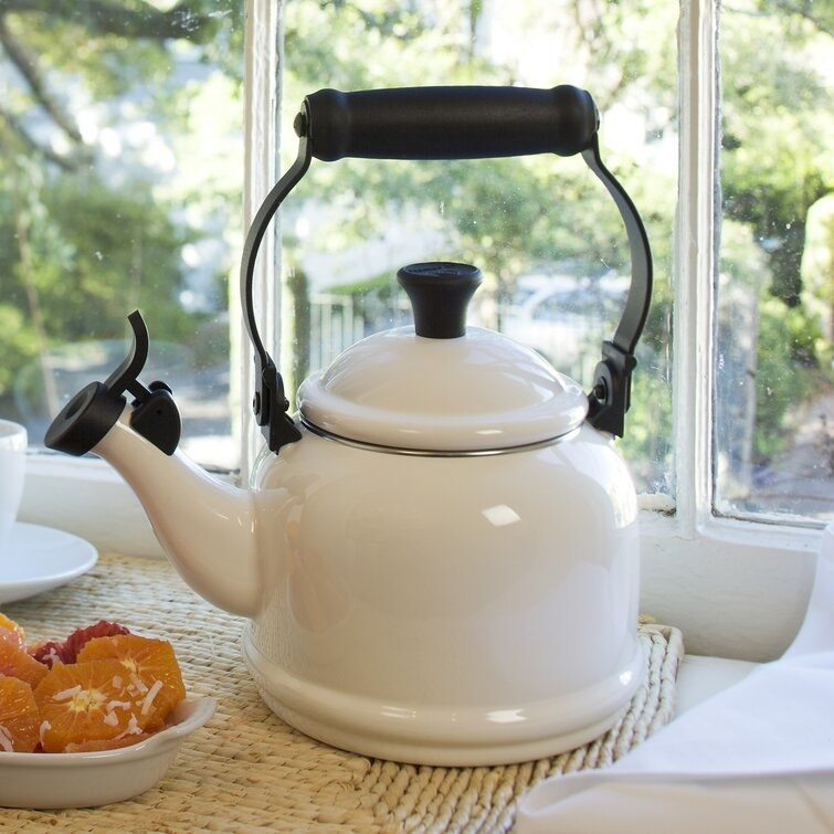 the ceramic kettle in white next to a bowl of oranges