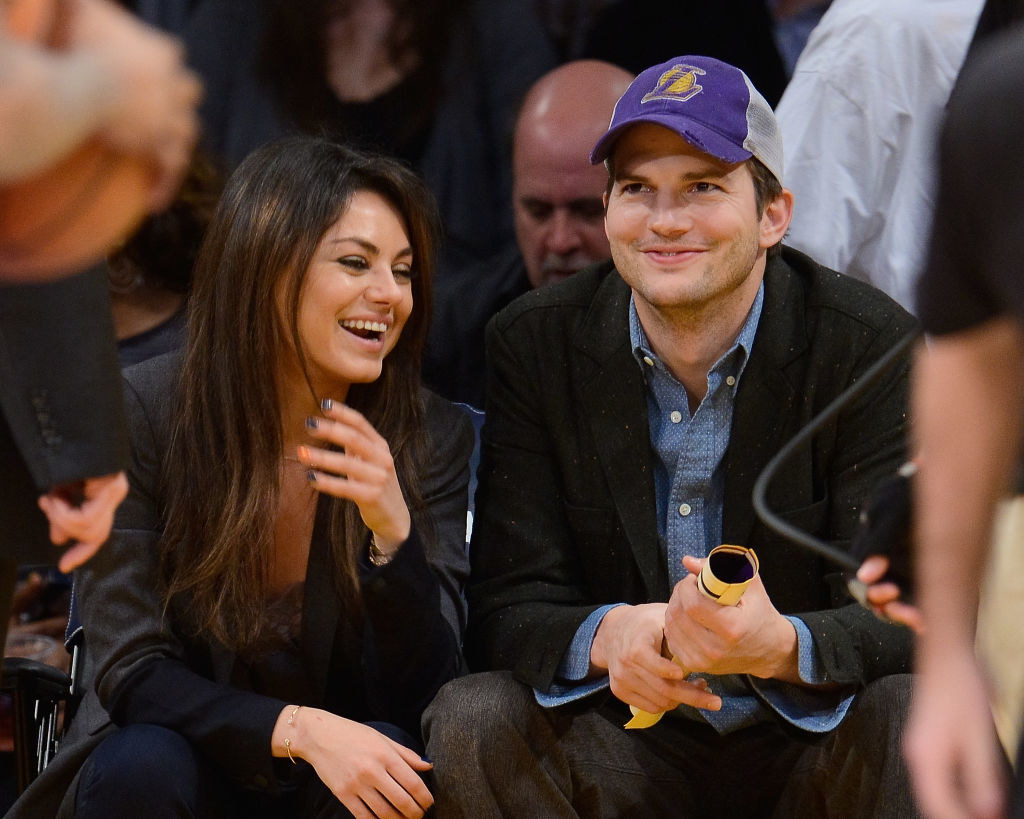 Ashton Kutcher (R) and Mila Kunis attend a basketball game between the Utah Jazz and the Los Angeles Lakers