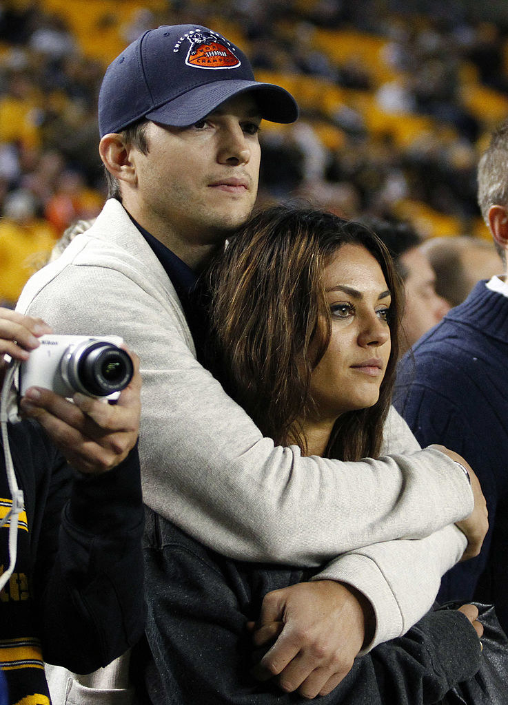Ashton Kutcher and Mila Kunis look on from the sidelines before the game between the Chicago Bears and the Pittsburgh Steelers