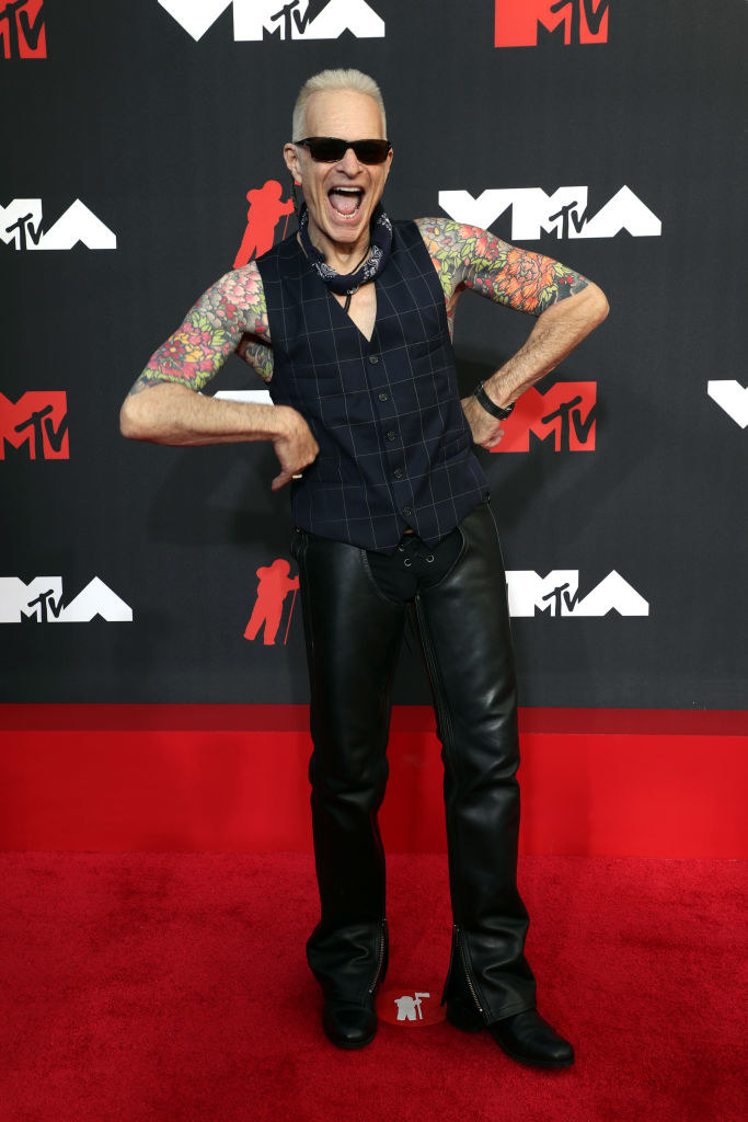 David Lee Roth on the red carpet in a black checkered vest and leather pants