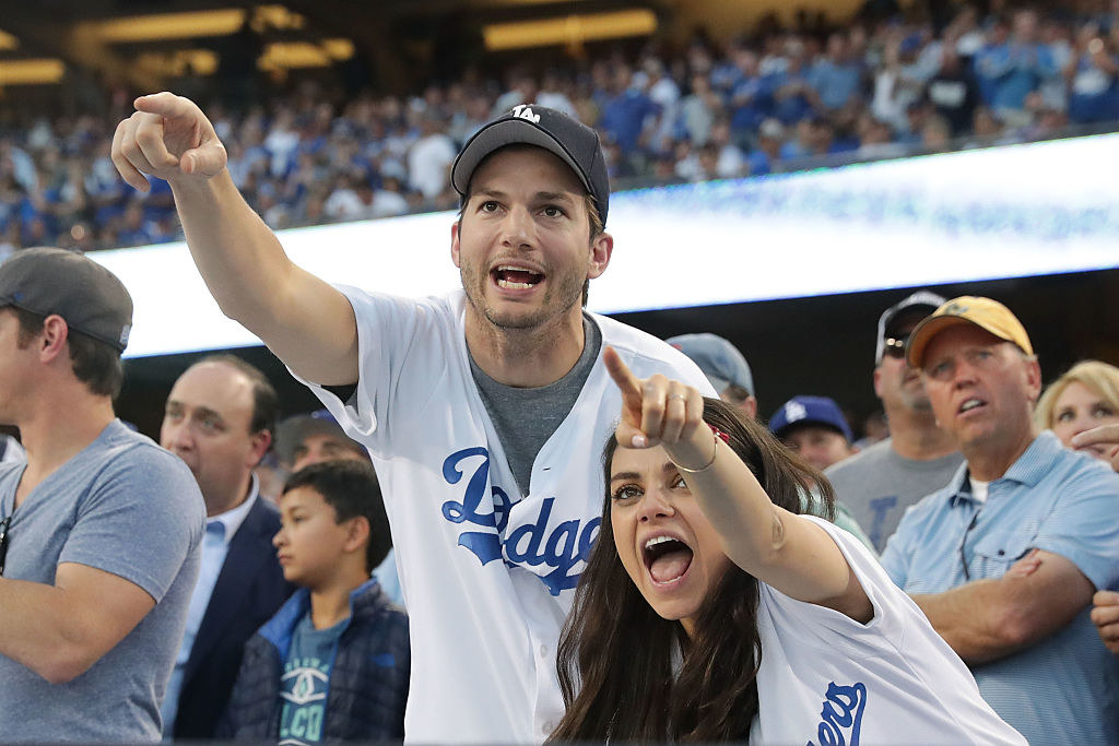 Mila Kunis (R) and Ashton Kutcher cheer in support of the Los Angeles Dodgers