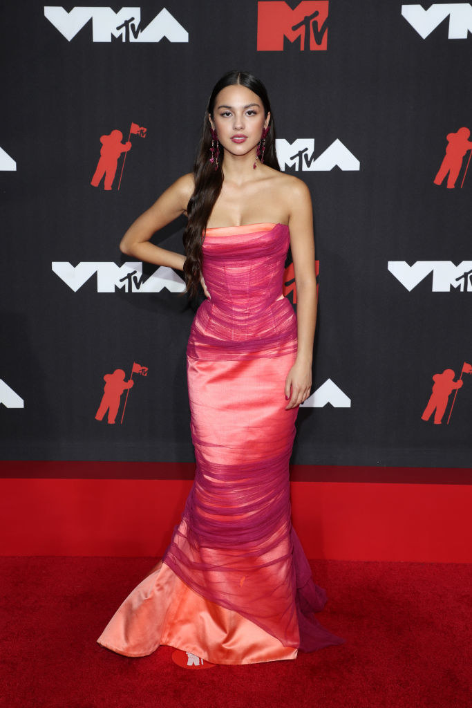 Olivia Rodrigo on the red carpet in a strapless orange gown with a magenta tulle overlay