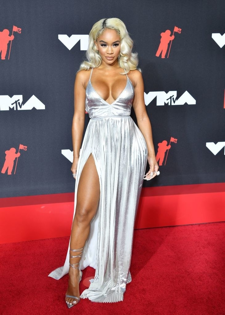 Saweetie on the rest carpet in a flowing, low cut silver gown
