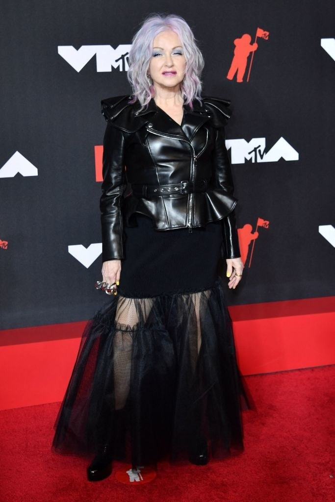 Cyndi Lauper on the red carpet in a black leather jacket and black tulle skirt
