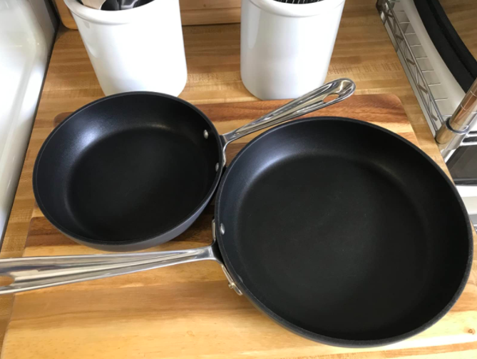 a reviewer's photo of the two pans on a kitchen counter top
