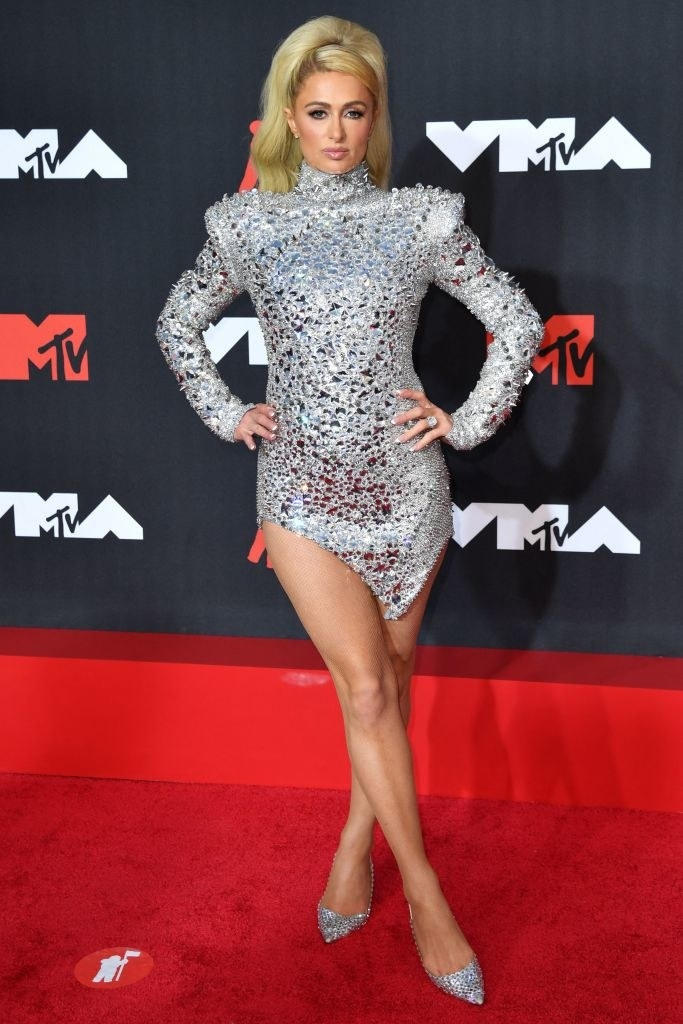 Paris Hilton on the red carpet in a short futuristic-looking silver dress