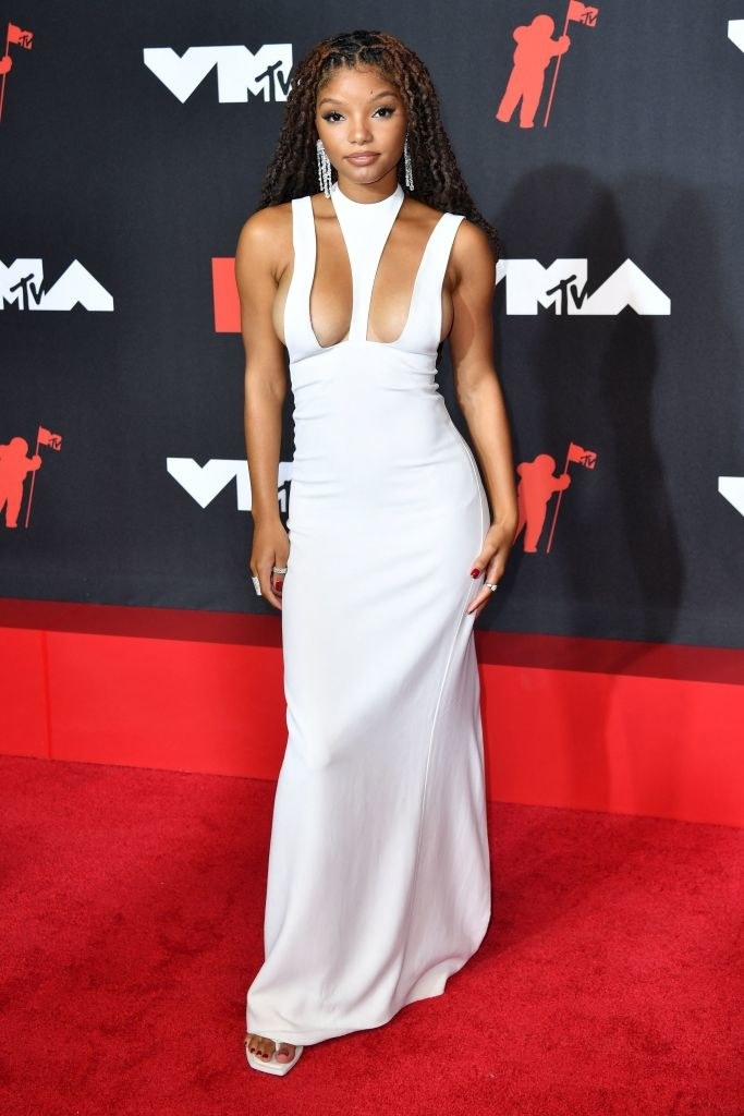 Halle Bailey on the red carpet in a white gown with cutouts on the bust