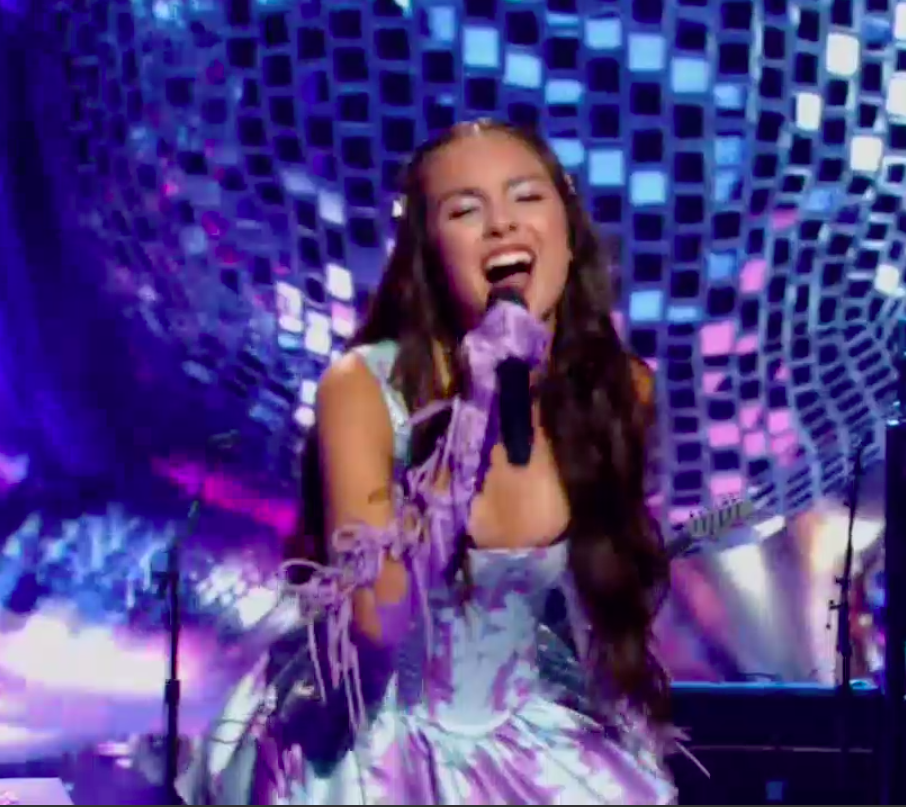 Olivia singing into the microphone with her eyes closed