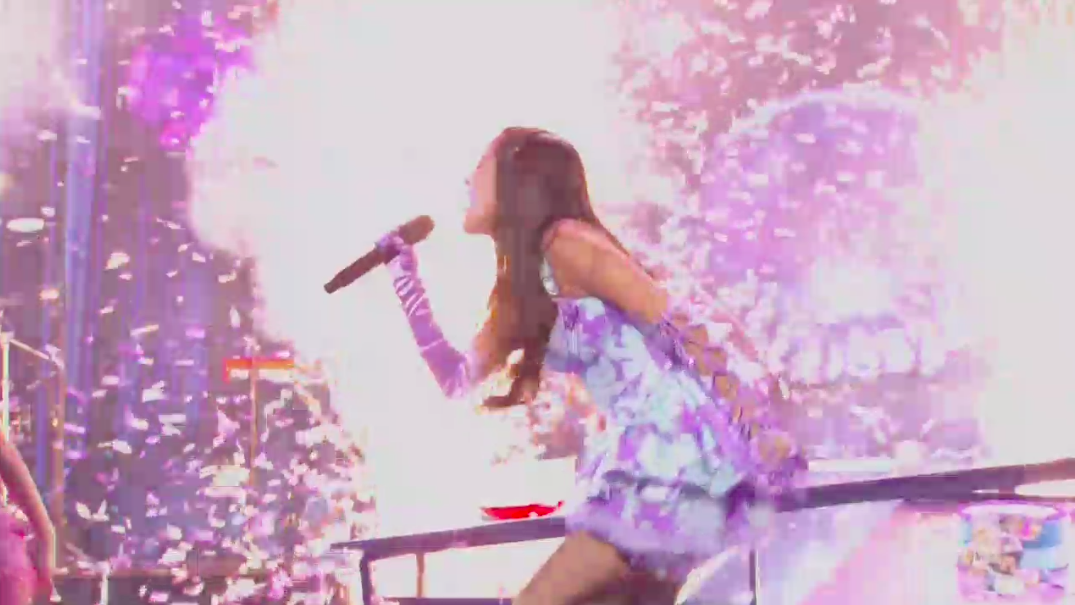 Olivia singing intensely and surrounded by glitter