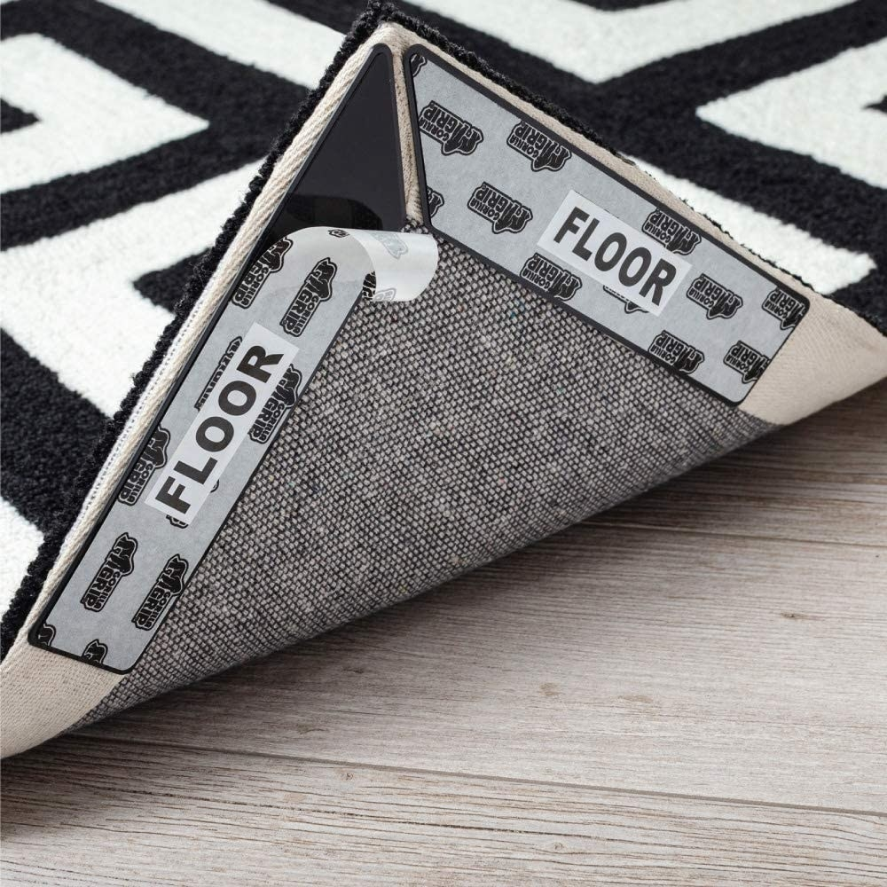 A image of grippers on an area rug being placed down on hardwood floors