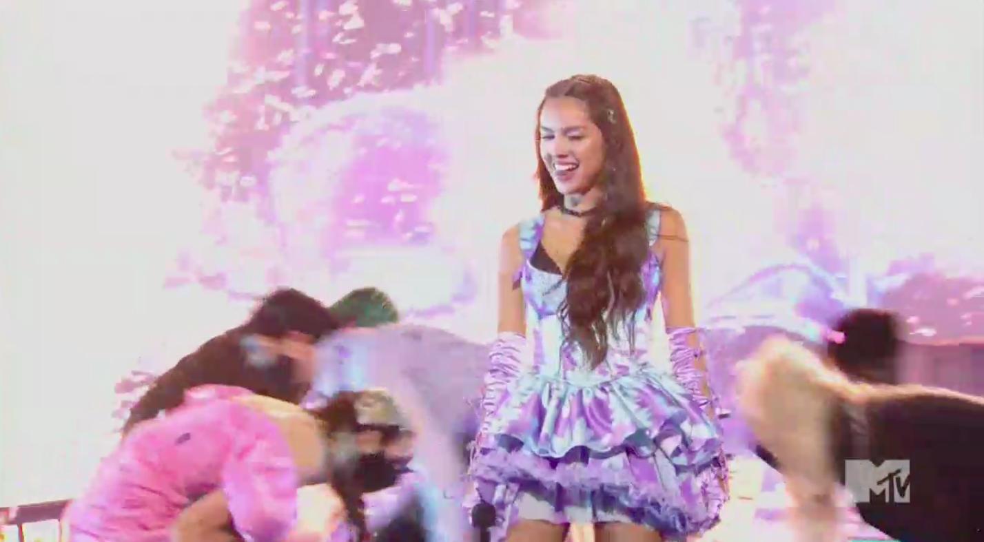 Olivia smiling onstage with her background dancers kneeling around her