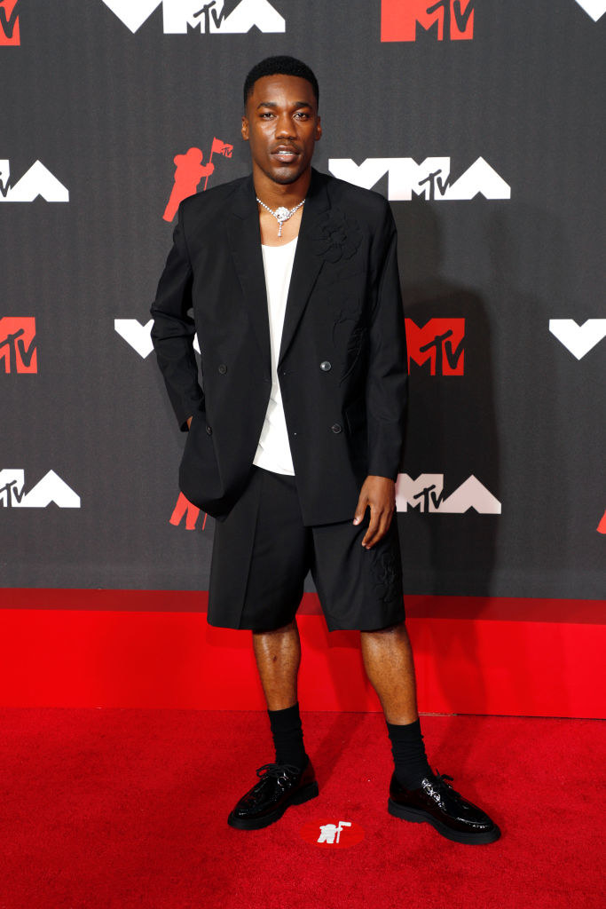 Giveon on the red carpet in a black suit jacket with black shorts