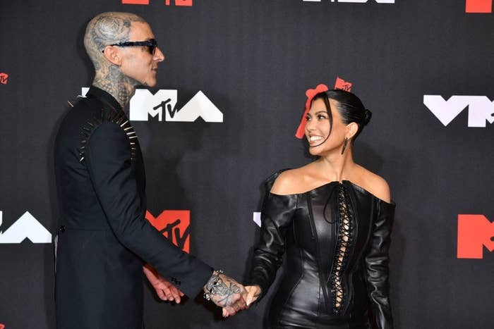 Travis Barker and Kourtney Kardashian hold hands as they arrive for the 2021 MTV Video Music Awards