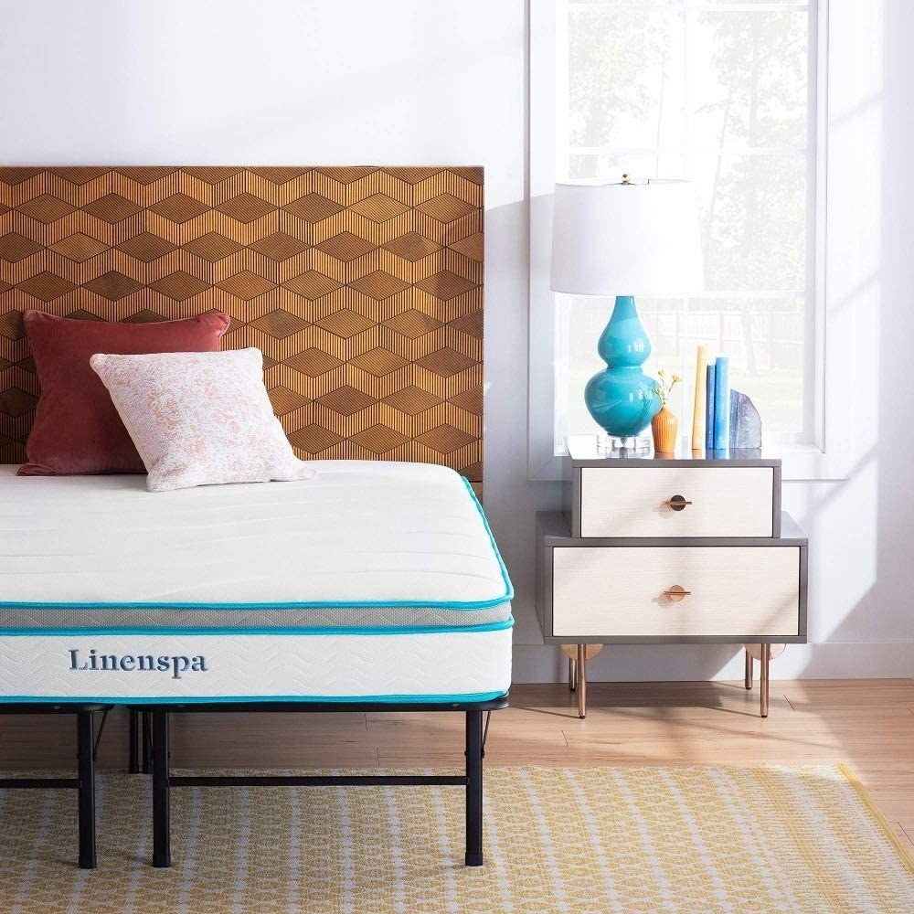 """White mattress with blue pipping and """"linenspa"""" on the side"""