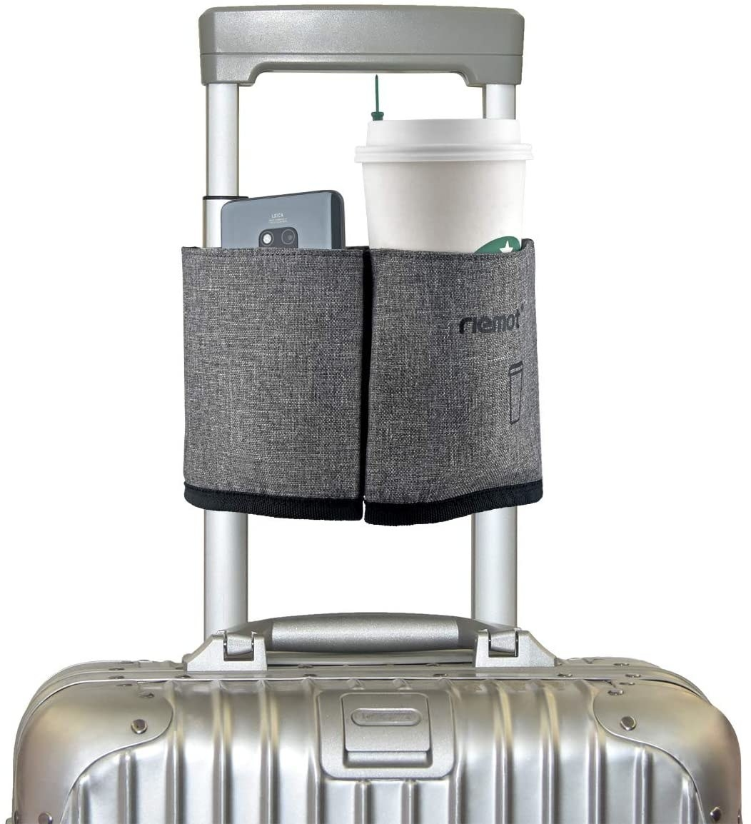 A photo of the gray cup caddy holding a Starbucks coffee and cellphone attached to a carry-on suitcase handle