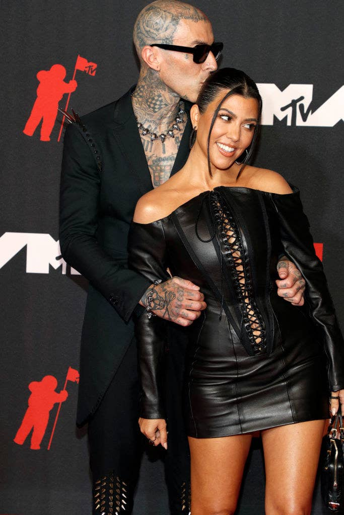 (L-R) Travis Barker with his arms around Kourtney Kardashian as he kisses her head
