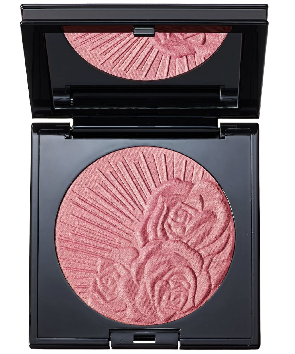 The pressed pink powder has roses and beams and is set in a circular pan in a black square container