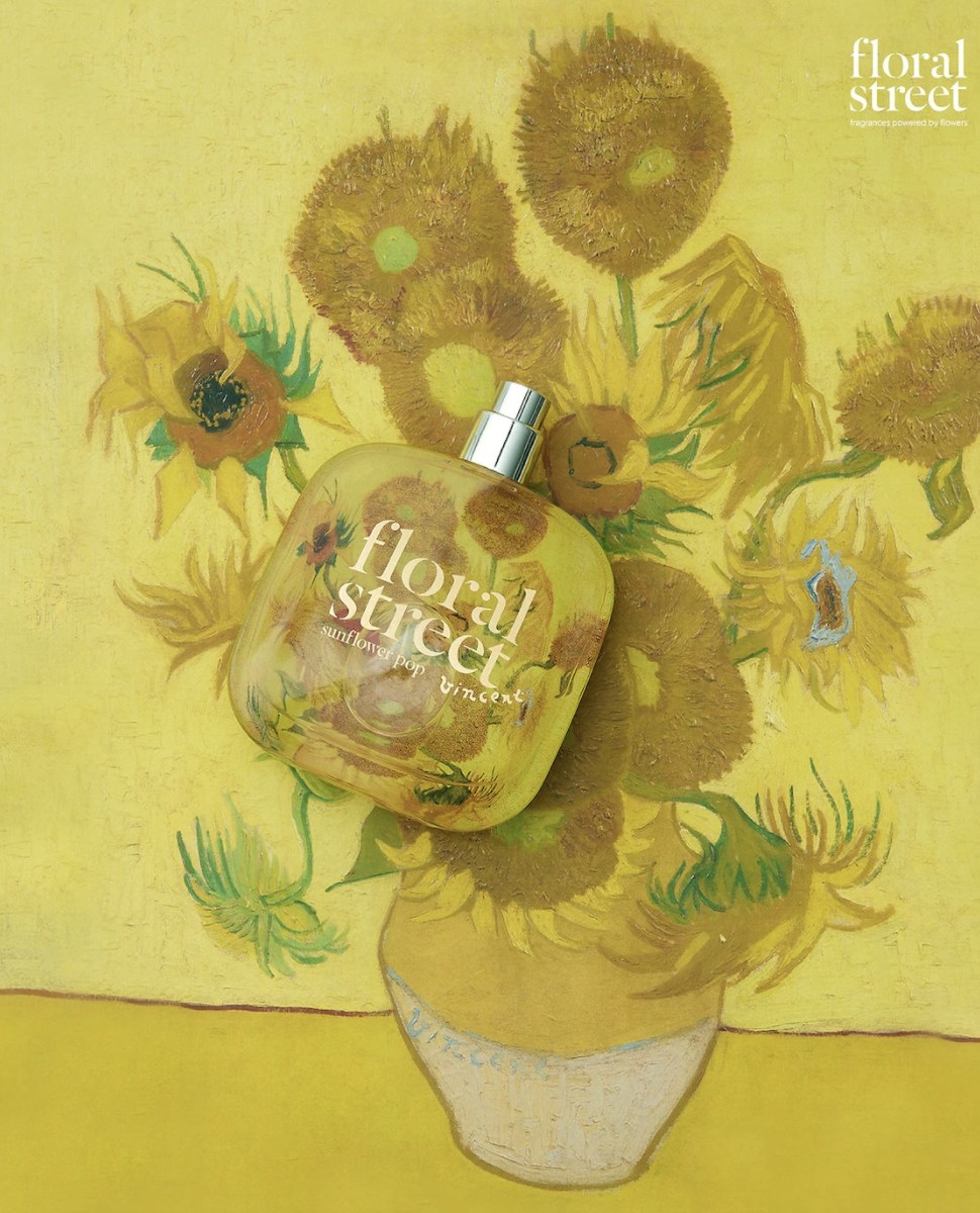 """The clear round edged square bottle says """"foral street"""" and is on top of Van Gogh's sunflower painting"""