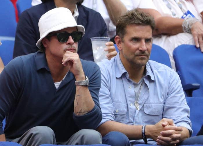 Brad Pitt, wearing a bucket hat, sitting next to Bradley Cooper