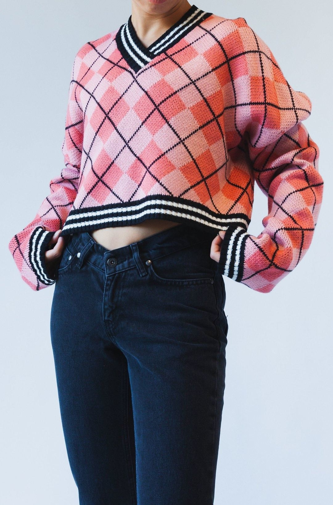model wearing the pink cropped sweater with dark wash jeans